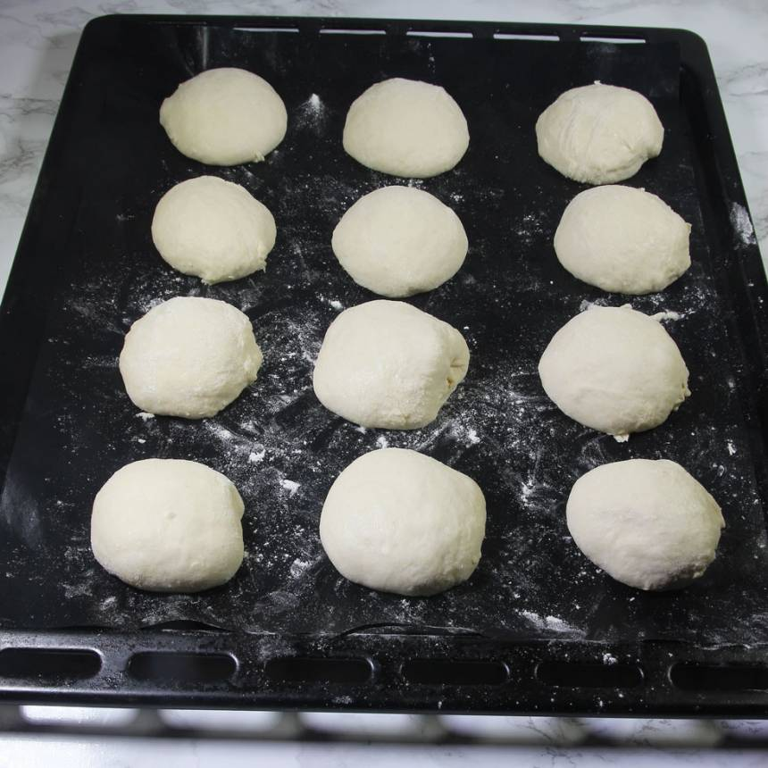 2. Dela degen i ca 20 bitar. Forma dem till runda bullar med mjölade händer. Lägg dem på en plåt med bakplåtspapper. Låt dem jäsa under bakduk i ca 30 min. Sätt ugnen på 250 grader.