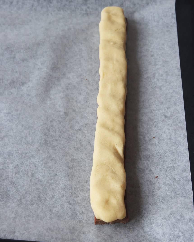 4. Rulla ut längderna, ca 25 cm långa. Lägg dem ovanpå raderna med choklad och platta till dem lite med fingrarna.
